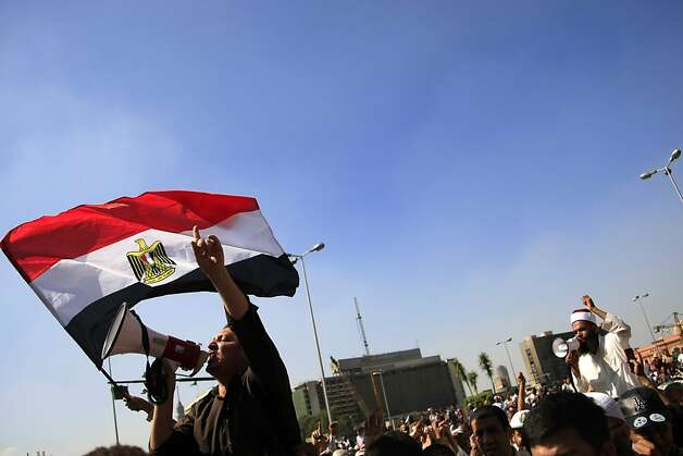 Protesters chant slogans and wave an Egyptian flag in Tahrir Square in Cairo, Egypt, Friday, Oct. 12, 2012. Supporters of Egypt's new Islamist president stormed a stage erected by opposition activists, smashed loudspeakers and tore the structure down during competing protests Friday in Cairo. The scuffles between supporters and opponents of President Mohammed Morsi reflect deep political divisions among the country's 82 million people, more than a year after the popular uprising that toppled Hosni Mubarak. (AP Photo/Khalil Hamra) Photo: Khalil Hamra, Associated Press