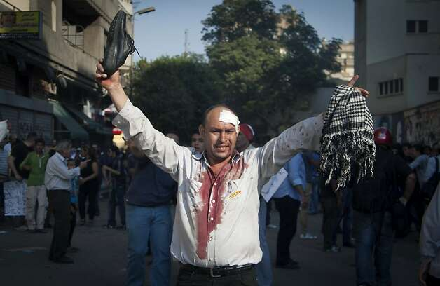 A wounded protester holds up his shoe in front of Muslim brotherhood supporters, not seen, after scuffles broke out between groups of protesters in Tahrir square when chants against the new Islamist president angered some in the crowd in Cairo, Egypt, Friday, Oct. 12, 2012. Thousands of supporters and opponents of Egypt's new Islamist president clashed in Cairo's Tahrir Square on Friday, hurling stones and concrete and swinging sticks at each other in the first such violence since Mohammed Morsi took office more than three months ago.(AP Photo/Khalil Hamra) Photo: Khalil Hamra, Associated Press