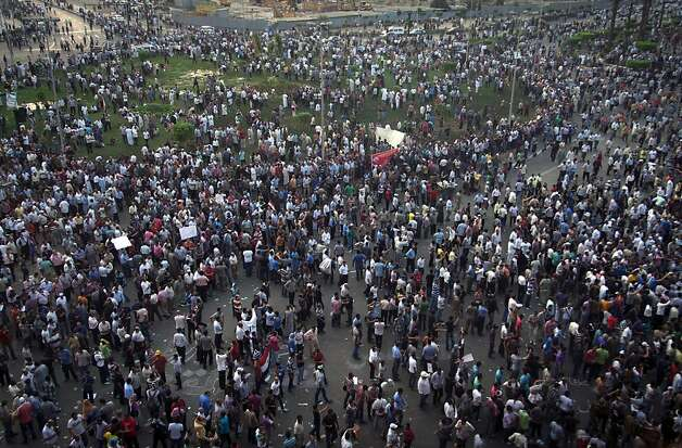 Protesters gather in Tahrir square in Cairo, Egypt, Friday, Oct. 12, 2012. Thousands of supporters and opponents of Egypt's new Islamist president clashed in Cairo's Tahrir Square on Friday, hurling stones and concrete and swinging sticks at each other in the first such violence since Mohammed Morsi took office more than three months ago.(AP Photo/Khalil Hamra) Photo: Khalil Hamra, Associated Press