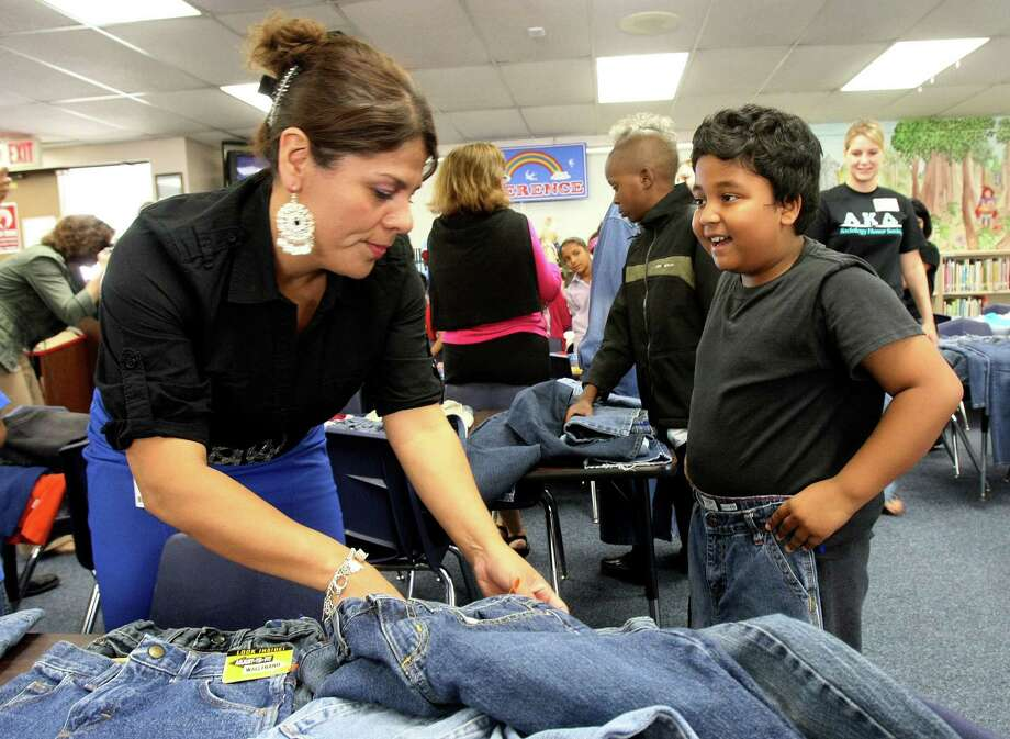 Maria Mendez, an instructional support teacher with the Northside Independent School District, helps Pratik Gazmere, 10, find jeans Friday at Glenoaks Elementary School. Photo: Helen L. Montoya, San Antonio Express-News / ©SAN ANTONIO EXPRESS-NEWS