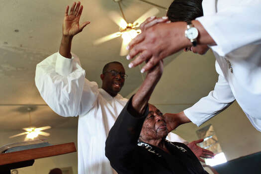"The oldest Pelham resident and native, Beatrice ""Aunt Bea"" Gee Beaty, 95, prays with Pastor of Rosa Kea, right, of Killeen, and her son, Tony Kea, left, during the Easter service at AME Brown Chapel. The next day, an explosion in Aunt Bea's trailer critically injured her and she passed away a week later. Photo: Lisa Krantz, San Antonio Express-News / © 2012 San Antonio Express-News"