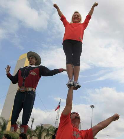 Amanda Christianson is help up by John Stewart next to Big Tex for a friend, not shown, to take a photo of the pair at the State Fair of Texas in Dallas, Friday, Oct. 12, 2012. Photo: LM Otero, Associated Press / AP