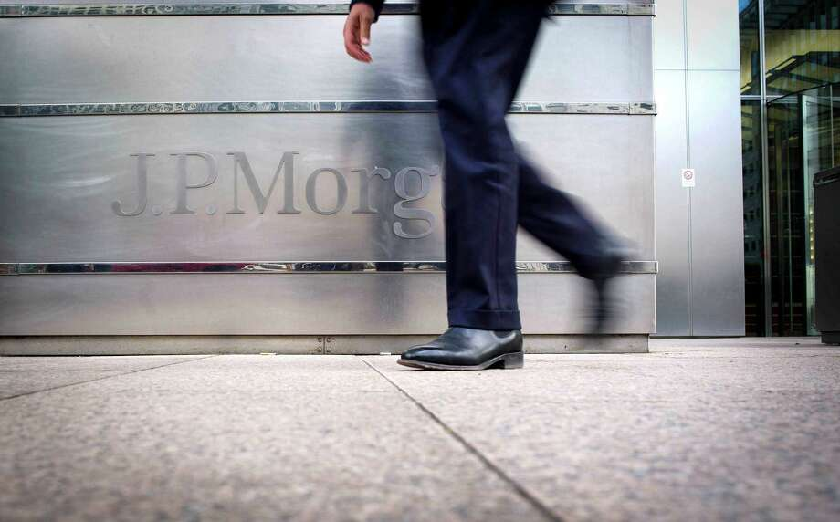 FILE - In this Aug. 8, 2012, file photo, a banker walks past JPMorgan Chase offices in London.  JPMorgan Chase, the country's biggest bank by assets, reported a record quarterly profit Friday, Oct. 12, 2012. The bank said it made $5.3 billion in earnings for common shareholders, a widely used measurement, from July through September, up 36 percent from the same period a year ago.(AP Photo/dapd,Timur Emek) Photo: Timur Emek