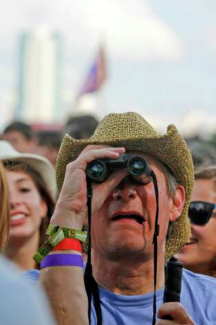A music fan gets a closer look with binoculars at the first day of the Austin City Limits Music Festival on Friday, Oct. 12 2012 in Austin, Texas. Photo: Jack Plunkett, Associated Press / Invision