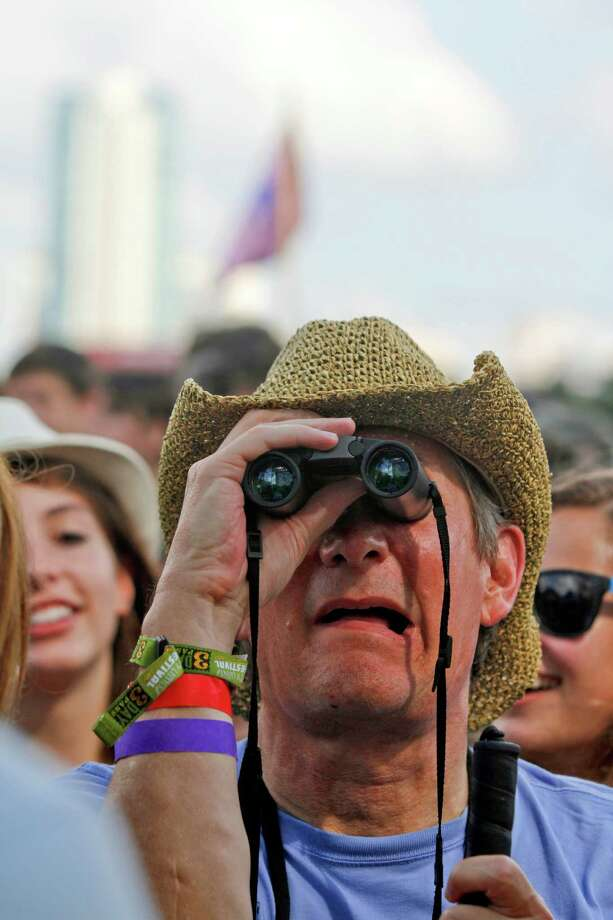 A music fan gets a closer look with binoculars at the first day of the Austin City Limits Music Festival on Friday, Oct. 12 2012 in Austin, Texas.(Photo by Jack Plunkett/Invision/AP) Photo: Jack Plunkett, Associated Press / Invision