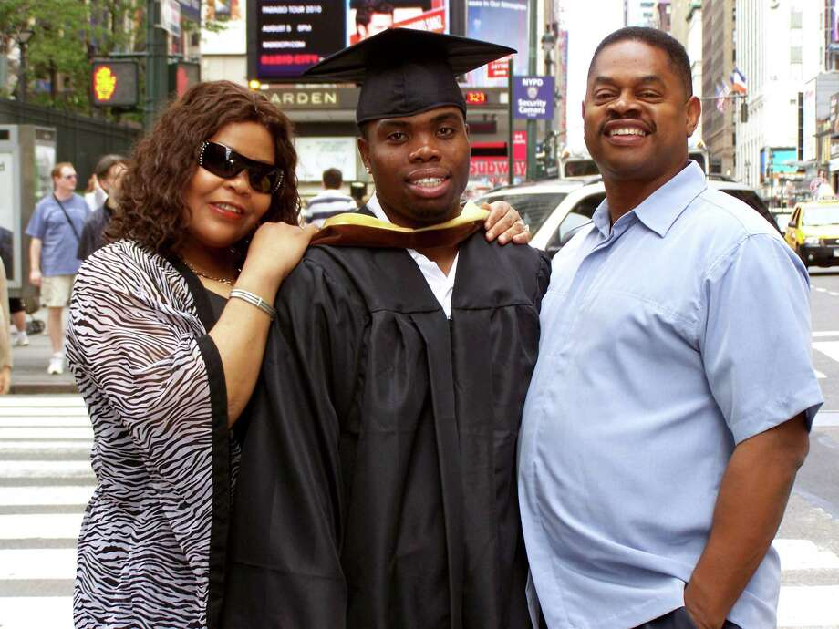 Dawayne Cobb, the 24-year-old Bridgeport resident found dead in his car parked Thursday, is pictured here with his foster parents, Michael and JoAnne Cobb of Shelton on his college graduation day. Dawayne graduated from Iona College with a bachelr's degree in finance in 2009. He was Bridgeport's 20th homicide victim of 2012. Photo: Contributed Photo / Connecticut Post Contributed