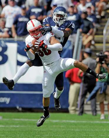 North Carolina State's Brandan Bishop, front, intercepts a pass intended for Connecticut's Geremy Davis during the second half of North Carolina's 10-7 victory in an NCAA college football game in East Hartford, Conn., on Saturday, Sept. 8, 2012. (AP Photo/Fred Beckham) Photo: Fred Beckham, Associated Press / Associated Press