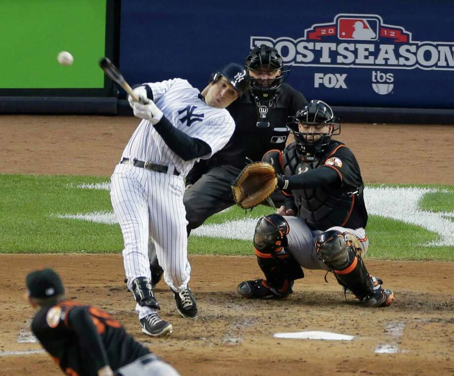 New York Yankees' Mark Teixeira hits a single against Baltimore Orioles pitcher Jason Hammel during the fifth inning in Game 5 of the American League division baseball series on Friday, Oct. 12, 2012, in New York. Orioles' catcher Matt Wieters and home plate umpire Mike Everitt watch the hit. (AP Photo/Peter Morgan) Photo: Peter Morgan / AP