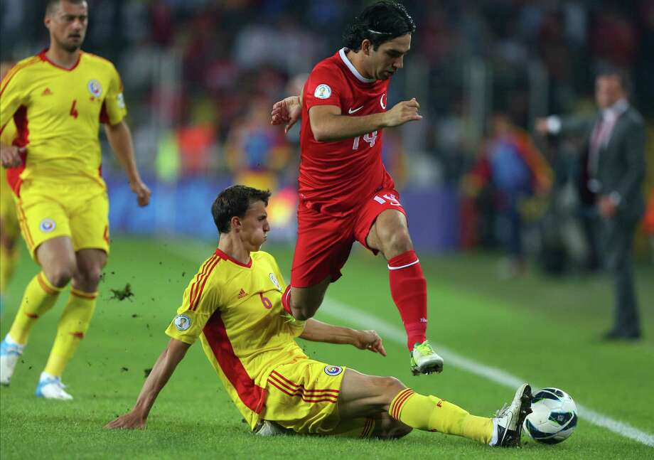 Turkey's Arda Turan, top, is challenged by Romania's Vlad Iulian Chiriches during their World Cup  qualifying soccer match at Sukru Saracoglu Stadium in Istanbul, Turkey Friday, Oct. 12, 2012. (AP Photo) / AP