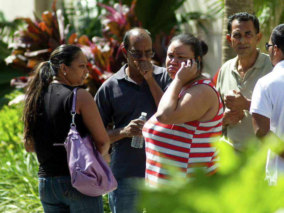 Unidentified family members of Robert Budhoo, who is missing after a parking garage collapsed at the Miami Dade College West campus in Doral, Fla., wait for results of the search through the rubble Thursday, Oct. 11, 2012, in Doral. (AP Photo/J Pat Carter) Photo: J Pat Carter