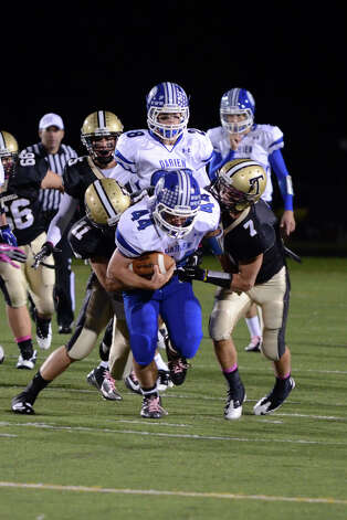 Darien's Christian Bognar (44) carries the ball as Trumbull's Daniel Paolino (11) and Thomas Hayduk (7) defend during the football game at Trumbull High School on Friday, Oct. 12, 2012. Photo: Amy Mortensen / Connecticut Post Freelance