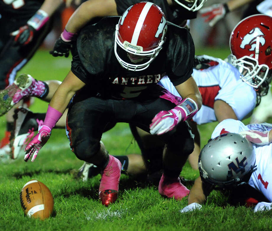 Masuk's Joe Damota reaches to recover the ball which was lost by New Fairfield's #1 Joe Pacheco, during boys football action in Monroe, Conn. on Friday October 12, 2012. Photo: Christian Abraham / Connecticut Post
