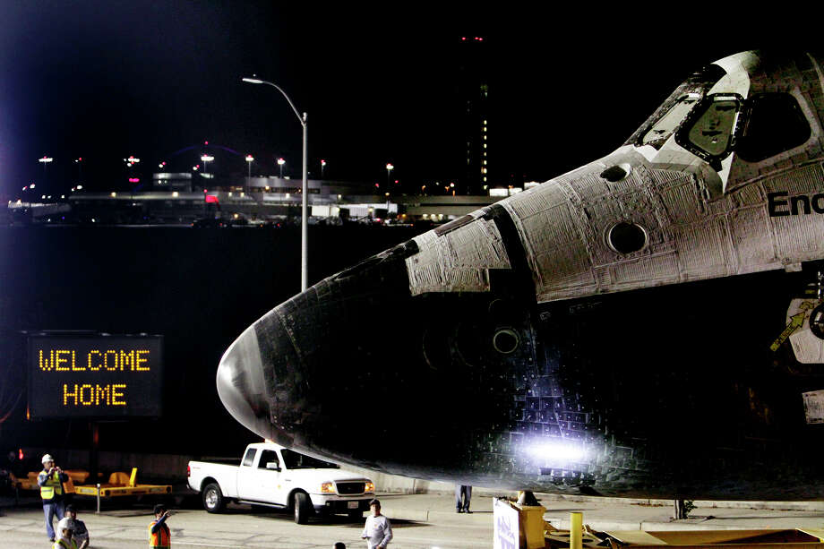 A welcome home sign is displayed on the turn as space shuttle Endeavour leaves Los Angeles International Airport hangar onto the streets in Los Angeles on Friday, Oct. 12, 2012. Endeavour's 12-mile road trip kicked off shortly before midnight Thursday as it moved from its Los Angeles International Airport hangar en route to the California Science Center, its ultimate destination, said Benjamin Scheier of the center. (AP Photo/Los Angeles Times, Lawrence K. Ho, Pool) Photo: Lawrence K. Ho