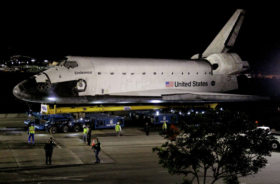 The space shuttle Endeavour leaves Los Angeles International Airport hangar onto the streets in Los Angeles on Friday, Oct. 12, 2012. Endeavour's 12-mile road trip kicked off shortly before midnight Thursday as it moved from its Los Angeles International Airport hangar en route to the California Science Center, its ultimate destination, said Benjamin Scheier of the center. (AP Photo/Los Angeles Times, Lawrence K. Ho) Photo: Lawrence K. Ho