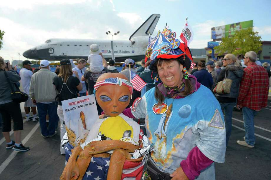 Vivianne Robinson Crowds poses in front of the Space Shuttle Endeavour before it is moved along city streets, Friday, Oct. 12, 2012, in Los Angeles. Endeavour's 12-mile road trip kicked off shortly before midnight Thursday as it moved from its Los Angeles International Airport hangar en route to the California Science Center, its ultimate destination, said Benjamin Scheier of the center. (AP Photo/Mark J. Terrill) Photo: Mark J. Terrill