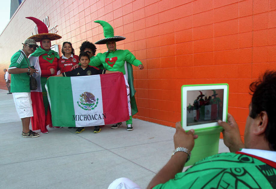 Mexico fan Melchor Gonzalez takes a photo of his family show their support before the FIFA World Cup qualifying match against Guyana at BBVA Compass Stadium Friday, Oct. 12, 2012, in Houston. Photo: Cody Duty, Houston Chronicle / © 2012 Houston Chronicle