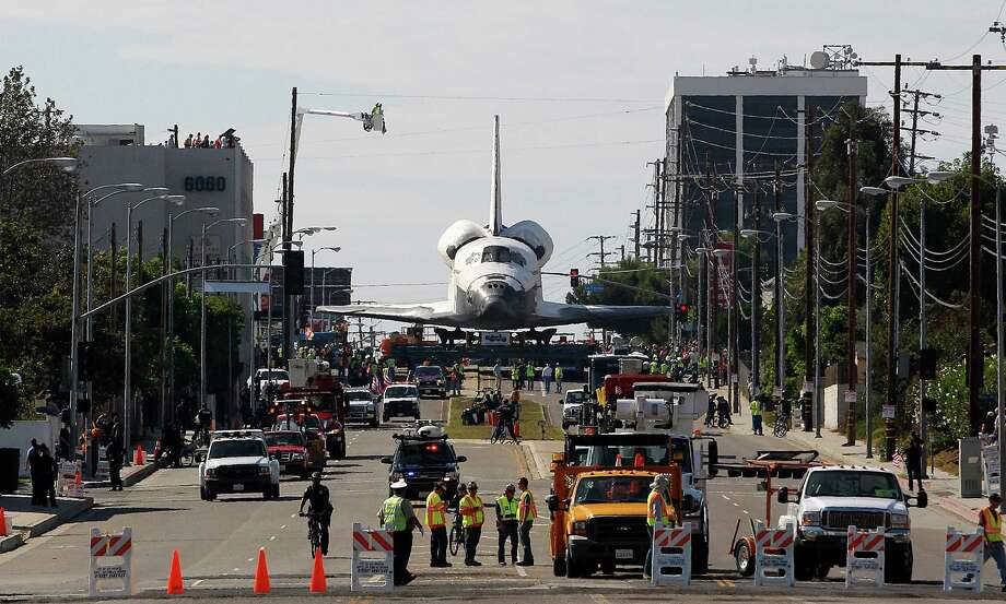 "The Space Shuttle Endeavour slowly moves along city streets on a 160-wheeled carrier in Los Angeles, Friday, Oct. 12, 2012. Endeavour's terrestrial journey began before dawn Friday when it departed from the Los Angeles International Airport, rolling on a 160-wheeled carrier past diamond-shaped ""Shuttle Xing"" signs. (AP Photo/Jae C. Hong) Photo: Jae C. Hong, Associated Press / AP"