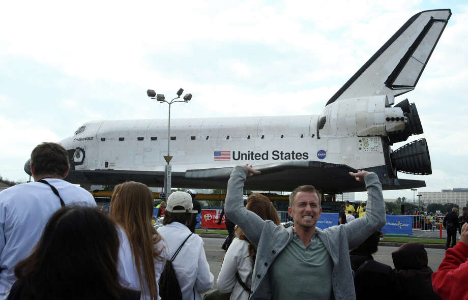 Joseph Duffield, 26, of Venice, Calif. pretends to hold up the space shuttle Endeavour as he poses for photos in front of the parked shuttle in Los Angeles on Friday, Oct. 12, 2012. Endeavour's 12-mile road trip kicked off shortly before midnight Thursday as it moved from its Los Angeles International Airport hangar en route to the California Science Center, its ultimate destination. (AP Photo/Los Angeles Times, Genaro Molina) Photo: Genaro Molina, Associated Press / Los Angeles Times