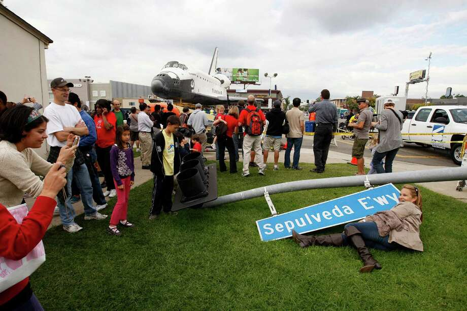 People pose for one another with a street sign that was removed to make way for the space shuttle Endeavour, behind them, during its transport from LAX to the California Science Center in Exposition Park where it will be on permanent public display on October 12, 2012 in Los Angeles, California. Photo: David McNew, Getty Images / 2012 Getty Images
