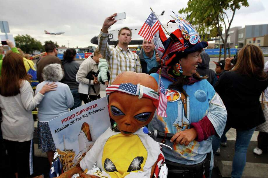 Vivian Robinson dresses up and carries a model from the movie E.T. on her bicycle to see the space shuttle Endeavour as it is transported from Los Angeles International Airport (LAX) to the California Science Center in Exposition Park where it will be on permanent public display on October 12, 2012 in Los Angeles, California. Photo: David McNew, Getty Images / 2012 Getty Images