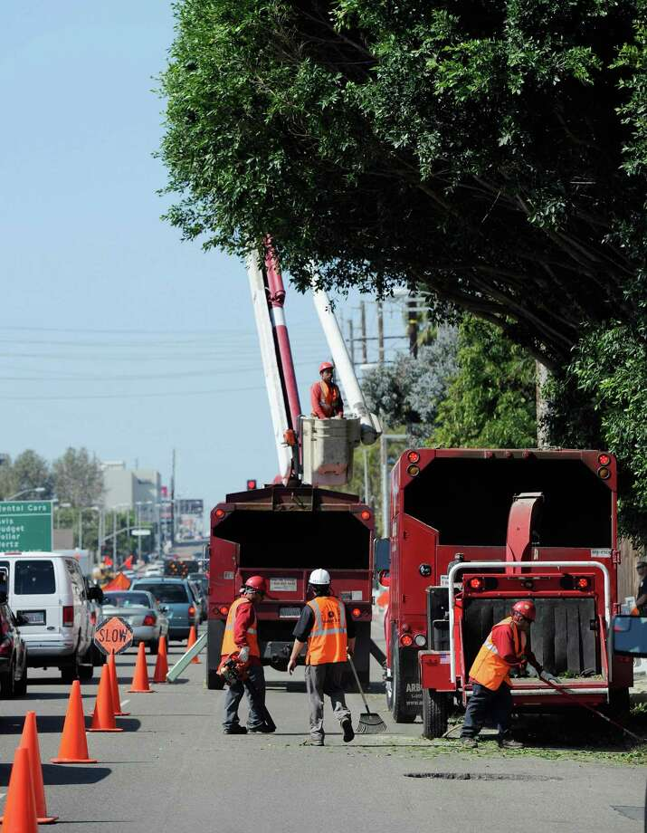 Tree trimmers cut down large branches of a tree that was protruding toward the street in a last-minute effort to clear hurdles along the route of the space shuttle Endeavour's as it journey's through the streets of Los Angeles County on October 12, 2012 in Los Angeles, California. Photo: Kevork Djansezian, Getty Images / 2012 Getty Images
