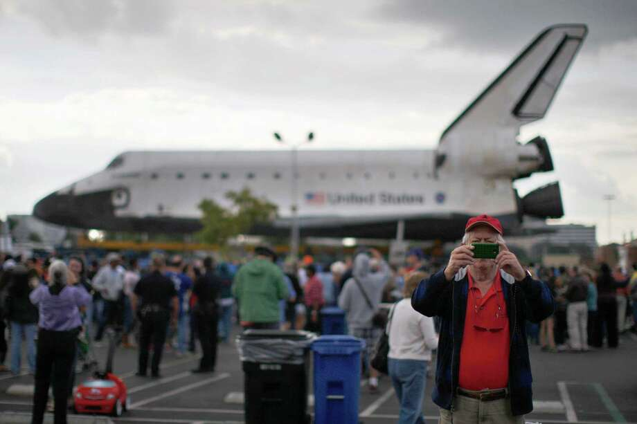 A man uses a smartphone to photograph himself near the space shuttle Endeavour during a break in its movement as it is transported from Los Angeles International Airport (LAX) to the California Science Center in Exposition Park where it will be on permanent public display on October 12, 2012 in Los Angeles, California. Photo: David McNew, Getty Images / 2012 Getty Images