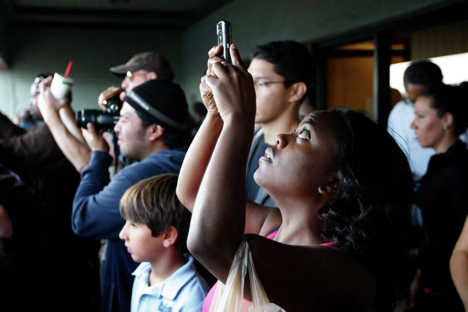 Members of the public photograph the space shuttle Endeavour from a business balcony during a break in its movement as it is transported from Los Angeles International Airport (LAX) to the California Science Center in Exposition Park where it will be on permanent public display on October 12, 2012 in Los Angeles, California. Photo: David McNew, Getty Images / 2012 Getty Images