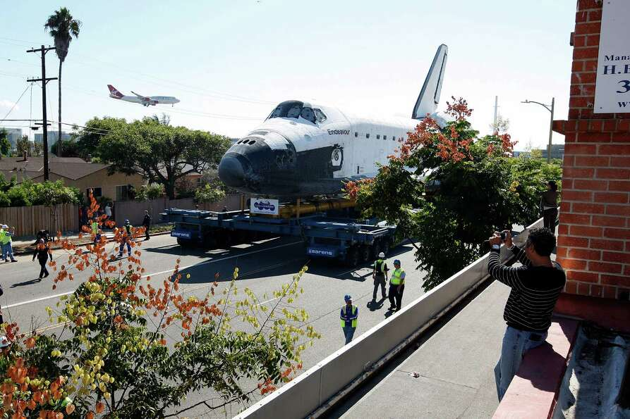 A jet lands at Los Angeles International Airport (LAX) as the space shuttle Endeavour is transported