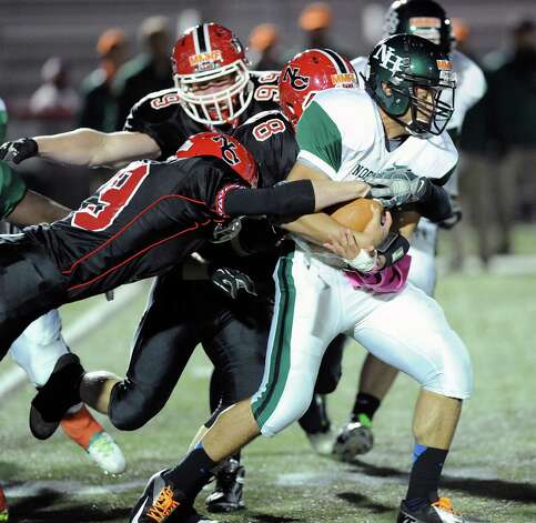 Norwalk quarterback Andy Lovo, right, gets tackled on a run by a group of New Canaan defensive players during the high School football game between New Canaan High School and Norwalk High School at New Canaan, Friday night, Oct. 12, 2012. Photo: Bob Luckey / Greenwich Time