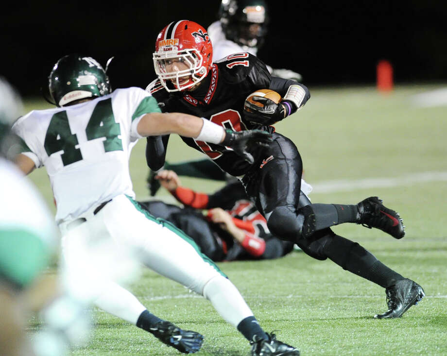 New Canaan running back Louis Hagopian, right, # 10, makes a cut in an attempt to get past James McInemey # 44 of Norwalk during the high School football game between New Canaan High School and Norwalk High School at New Canaan, Friday night, Oct. 12, 2012. Photo: Bob Luckey / Greenwich Time