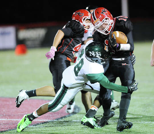 At left, Lance Lauture # 28 of Norwalk tackles New Canaan running back Louis Hagopian # 10 during the high School football game between New Canaan High School and Norwalk High School at New Canaan, Friday night, Oct. 12, 2012. Photo: Bob Luckey / Greenwich Time