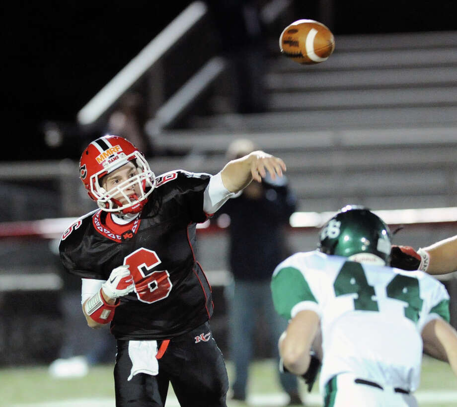 At left, New Canaan quarterback Teddy Bossidy # 6 throws while being pressured by Norwalk's James McInemey # 44 during the high School football game between New Canaan High School and Norwalk High School at New Canaan, Friday night, Oct. 12, 2012. Photo: Bob Luckey / Greenwich Time
