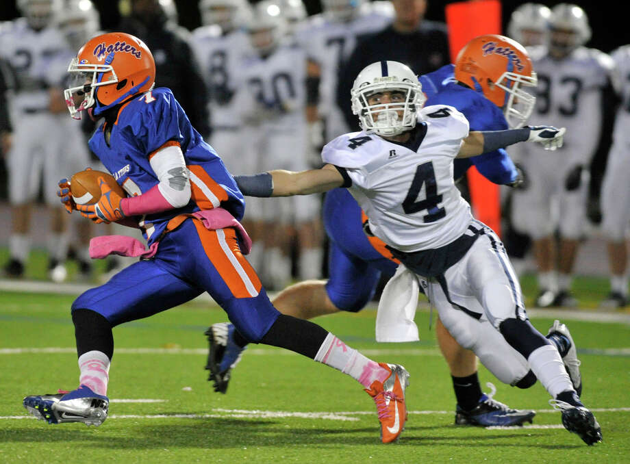 Staples' James Frusciante reaches for Danbury's Corey Chaffee as Chaffee runs for the Hatters' only touchdown during their game at Danbury High School on Friday, Oct. 12, 2012. Staples won, 51-6. Photo: Jason Rearick / The News-Times