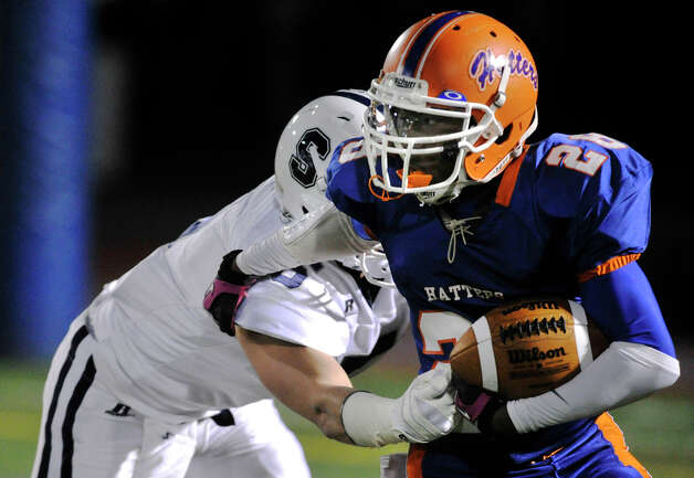 Danbury's Chris Latham runs with the ball while under pressure from Staples' Nick Kelly during their game at Danbury High School on Friday, Oct. 12, 2012. Staples won, 51-6. Photo: Jason Rearick / The News-Times