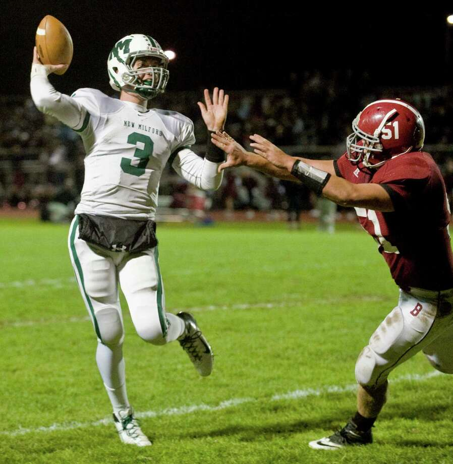 New Milford High School quarterback Connor Shanahan tries to get the pass off before being hit by Bethel High School's Peter Serencsics in a game at Bethel. Friday, Oct. 12, 2012 Photo: Scott Mullin / The News-Times Freelance