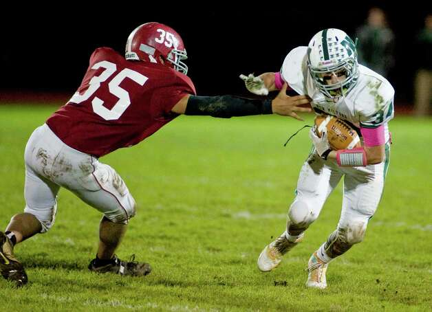Bethel High School's Sam Reyes tries to grab New Milford High School's Teven Leonard during a football game at Bethel. Friday, Oct. 12, 2012 Photo: Scott Mullin / The News-Times Freelance