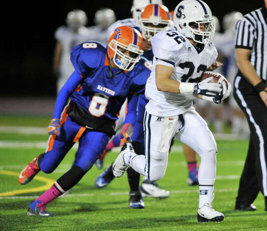 Staples' Greg Strauss runs with the ball while under pressure from Danbury's Alfred Valentine during their game at Danbury High School on Friday, Oct. 12, 2012. Staples won, 51-6. Photo: Jason Rearick / The News-Times
