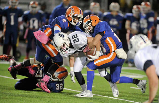 Staples' Joey Zelkowitz is brought down by Danbury's Elijah Duffy, left, and Tyler Harrington, right, during their game at Danbury High School on Friday, Oct. 12, 2012. Staples won, 51-6. Photo: Jason Rearick / The News-Times