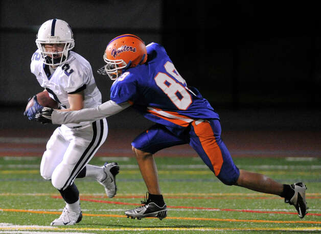 Staples' Will Johnson runs with the ball while under pressure from Danbury's Justin Placella during their game at Danbury High School on Friday, Oct. 12, 2012. Staples won, 51-6. Photo: Jason Rearick / The News-Times
