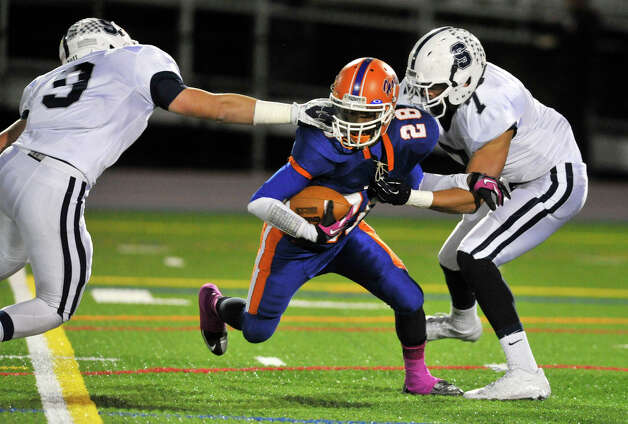 Danbury's Chris Latham is brought down by Staples' H Jared Levi, left, and Lance Lonergan during their game at Danbury High School on Friday, Oct. 12, 2012. Staples won, 51-6. Photo: Jason Rearick / The News-Times