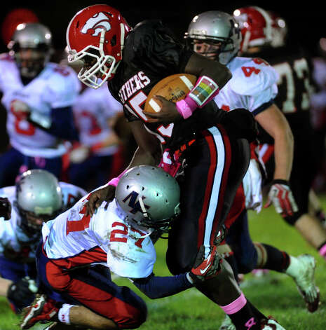 New Fairfield's #27 Al Costanzo attempts to tackle Masuk QB Maik Cummings, during boys football action in Monroe, Conn. on Friday October 12, 2012. Cummings was able to break free and carry the ball several more yards. Photo: Christian Abraham / Connecticut Post