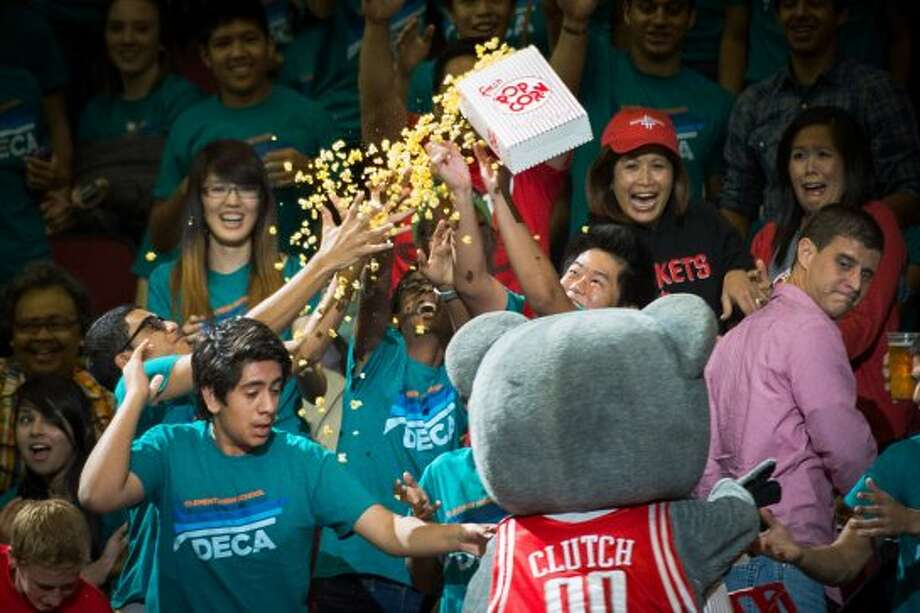 Fans reach for a box of popcorn tossed into the stands by Rockets mascot Clutch during the first half. (Smiley N. Pool / © 2012  Houston Chronicle)