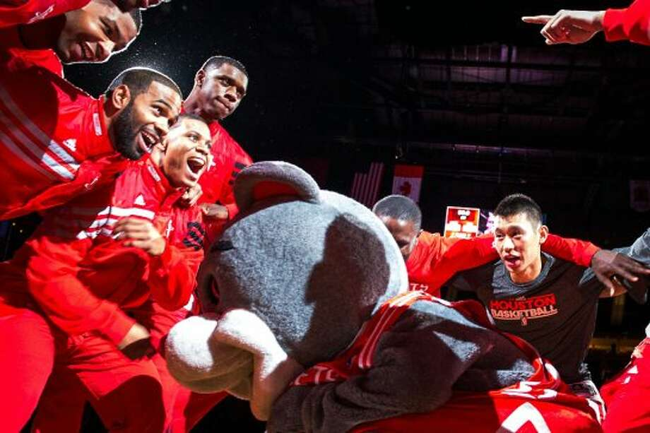 Rockets players huddle around mascot Clutch as a pregame festivity. (Smiley N. Pool / © 2012  Houston Chronicle)