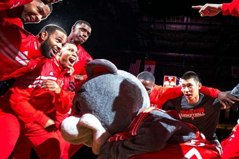 Rockets players huddle around mascot Clutch as a pregame festivity. (Smiley N. Pool / © 2012  Houston Chronicle)