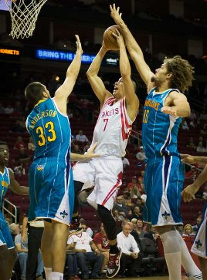 Rockets guard Jeremy Lin drives to the basket past  Hornets forward Ryan Anderson and center Robin Lopez. (Smiley N. Pool / © 2012  Houston Chronicle)