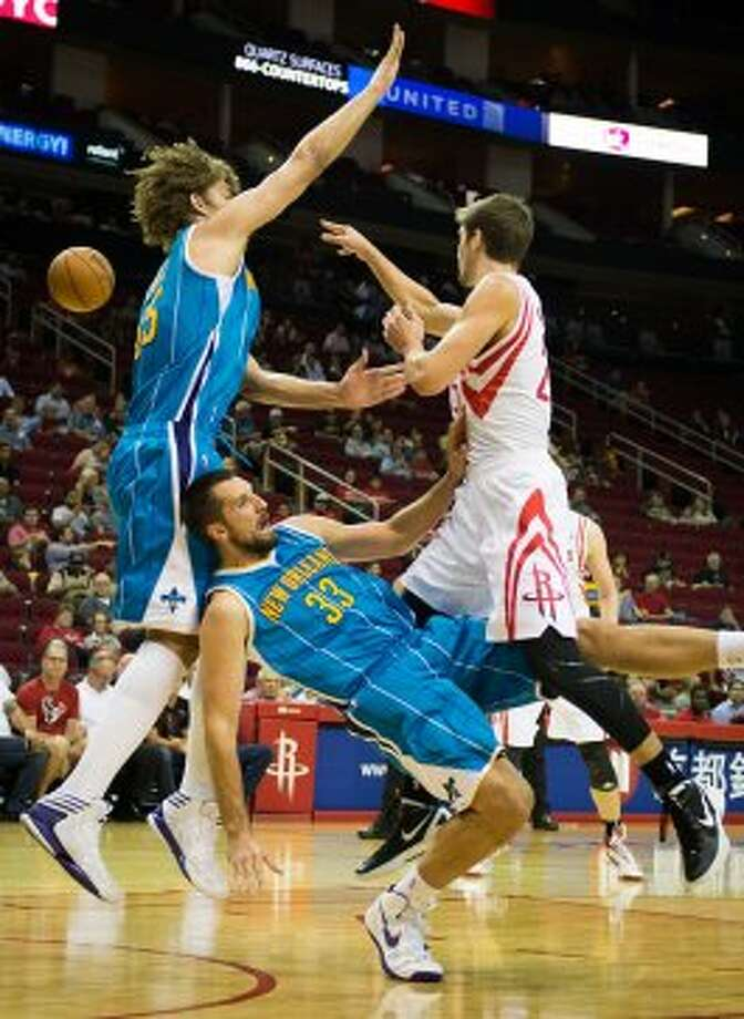 Rockets forward Chandler Parsons makes a pass as New Hornets forward Ryan Anderson tries to draw a charge. (Smiley N. Pool / © 2012  Houston Chronicle)