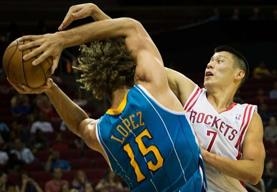 Rockets guard Jeremy Lin  fights for a rebound with Hornets center Robin Lopez. (Smiley N. Pool / © 2012  Houston Chronicle)