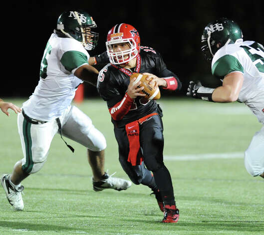 New Canaan quarterback Nick Cascione, center, splits two Norwalk defensive players during the high School football game between New Canaan High School and Norwalk High School at New Canaan, Friday night, Oct. 12, 2012. Photo: Bob Luckey / Greenwich Time