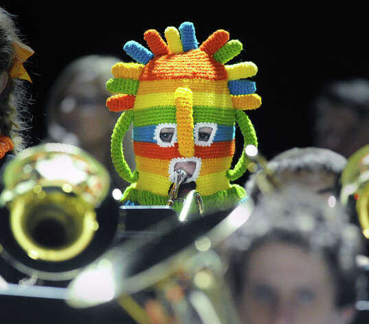 "New Canaan High School band member Levi Hardman, 17, a junior, wears a colorful hat while playing his trumpet during the high School football game between New Canaan High School and Norwalk High School at New Canaan, Friday night, Oct. 12, 2012. Hardman said he was new to the band and that new band members must wear the multi-colored ""initiation hat."" Photo: Bob Luckey / Greenwich Time"