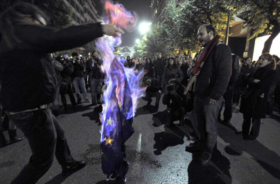 """FILE - Demonstrators burn an EU flag in this file photo dated Thursday Nov. 17, 2011, in Thessaloniki, Greece.  It is announced Friday Oct. 12, 2012, that the European Union has been awarded the Nobel Peace Prize for its efforts to promote peace and democracy in Europe, in the midst of the union's biggest crisis since its creation in the 1950s. The Norwegian prize committee said the EU receives the award for six decades of contributions """"to the advancement of peace and reconciliation, democracy and human rights in Europe. (AP Photo/ Nikolas Giakoumidis, File) Photo: Nikolas Giakoumidis / ap"""